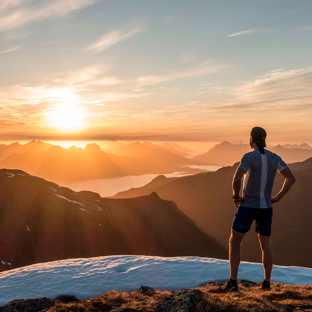 Kenn stands on a mountain top and looks at the midnight sun